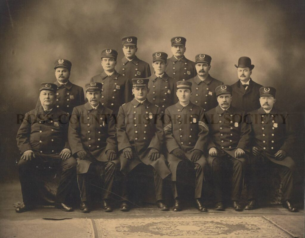 Photo of policemen from 1910 in period dress, seated and standing in rows
